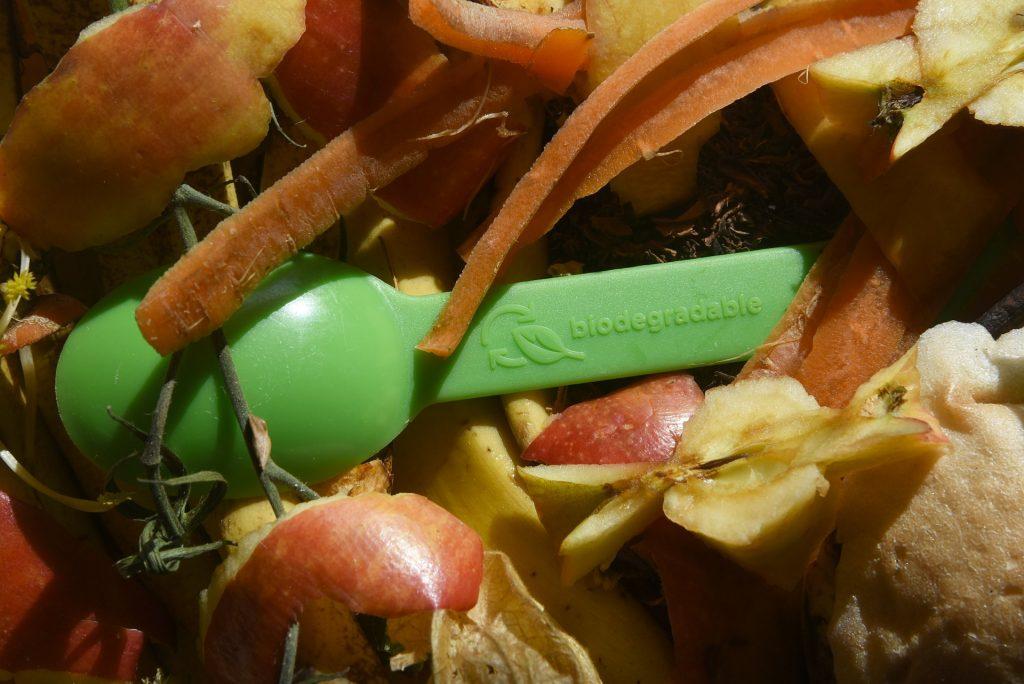 grüner Bioplastiklöffel im Kompost